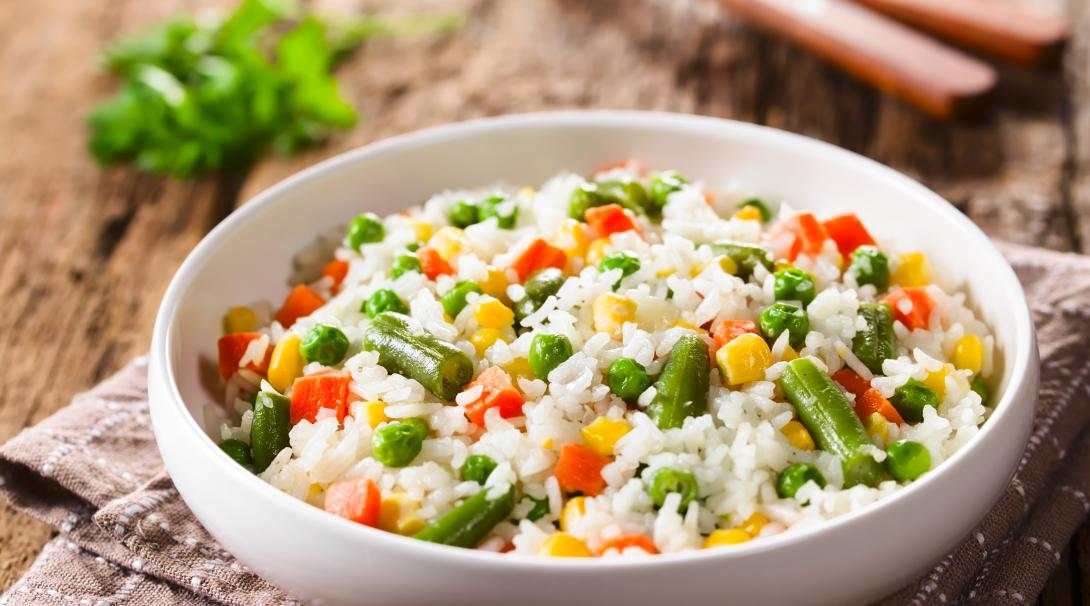 A bowl of cooked white rice with colourful vegetables
